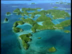 Track left over green shrub covered atolls surrounded by tropical blue seas Palau