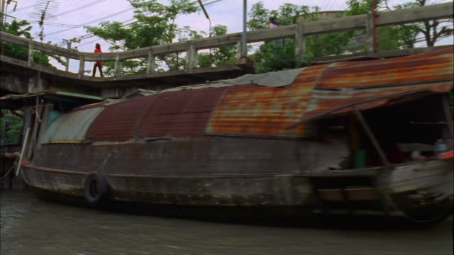 Track left past rusty moored boats on Chao Phraya river Available in HD.