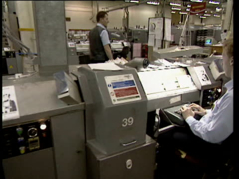 Track left past seated Royal Mail staff typing information in machines as letters past by