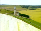 Track over Belle Tout Lighthouse on top of white cliffs people standing on cliff edge Beachy Head