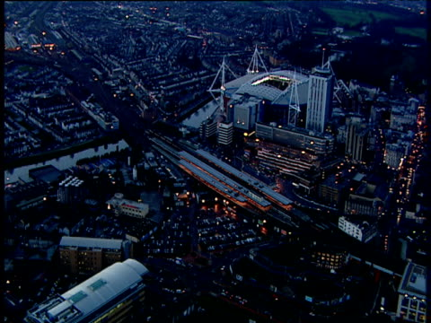 Track over city of Cardiff Millennium Stadium illuminated at night with roof open in background