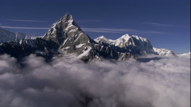 Track over mountain peaks protruding through a layer of cloud, Himalaya, Nepal. Available in HD.
