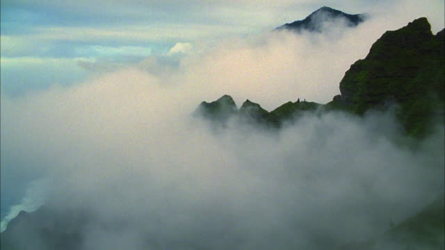 Track over mountain peaks through white cloud, Kauai Available in HD.