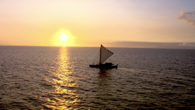 Track over Polynesian canoe sailing on Pacific ocean at sunset, Hawaii