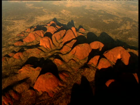 Track over red sandstone Olgas rising out of outback, Northern Territory, Australia