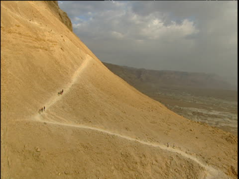 Track over sandy paths on rocky mountain few people walking the zigzag paths Masada