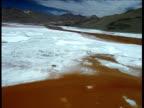 Track over soda encrusted orange salt lake, mountains in background, Bolivia