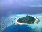 Track over tropical islands with jettys large blue circular atoll and sandy white beaches by island homes.