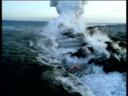 Track over waves crashing onto lava erupting from sea bed creating huge clouds of steam