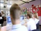 Track right behind teenagers wearing school uniform sitting at computers in classroom