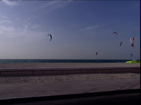 Track right from car past many colourful kites being flown on beach Dubai