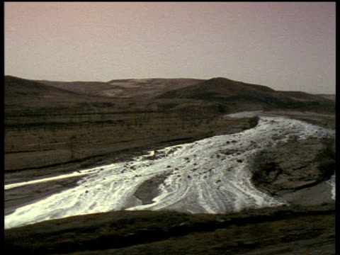 Track right from train across partly dried up muddy river in midst of barren landscape outskirts of Datong