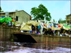 Track right past large barge docked on river acting as makeshift market place Democratic Republic of Congo