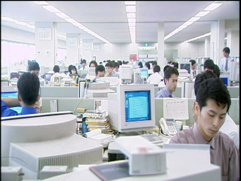 Track right past Tokyo financial workers seated and working in a long open-plan office full of computers
