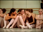 Track right past young female ballet dancers resting and gossiping by mirror, Seattle