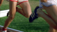 SLO MO CU DS Track runners' legs as they run around track