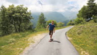 Track shot of teen on longboard ascending mountain road