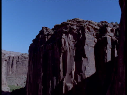 Track up over outcrop to reveal canyon in desert, Moab, Utah