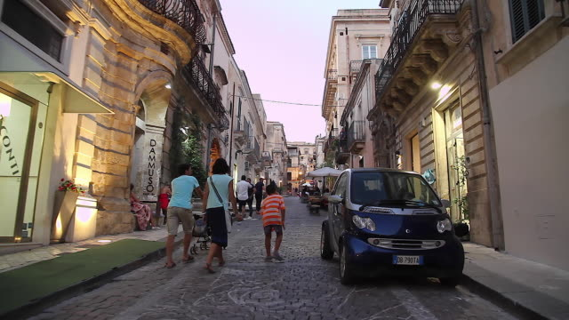 Tracking a family taking an early evening stroll along the beautiful streets of Noto, Sicily, Italy