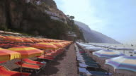 Tracking a sea of beach umbrellas and beach chairs lined up on picturesque Positano waterfront, Amalfi Coast, Italy