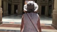 Tracking behind a female tourist admiring an arcade passing through classic Italian architecture, Rome