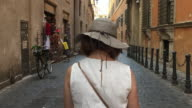 Tracking behind a female tourist walking down a cobble stoned, classic roman street, Rome