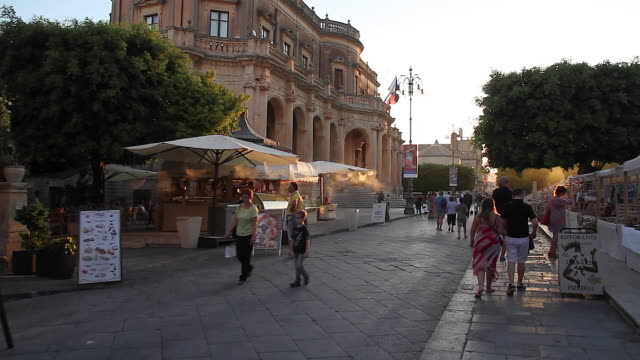 Tracking diners, restaurant tables and people strolling the the Piazza Municipal leading to the Ducezio Palace, Noto, Sicily, Italy