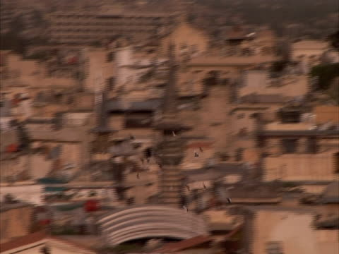 Tracking flock of birds flying over Arabic townscape, Umayyad mosque tower, Syria (sound available)