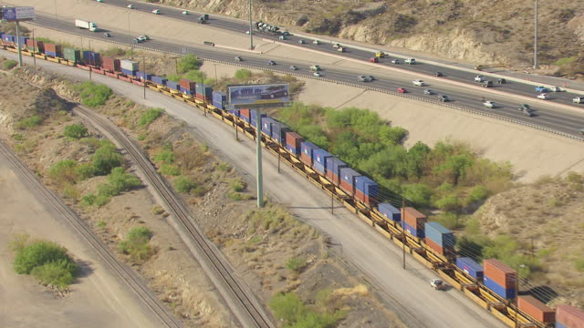 WS AERIAL tracking high over trains and highway / El Paso, Texas, United States