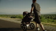 Tracking medium shot of man with baby carriage running on road / Cedar Hills, Utah, United States