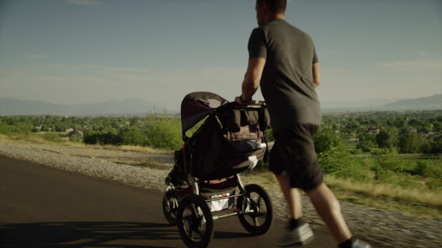Tracking medium shot of man with baby carriage running on road / Cedar Hills, Utah, United States