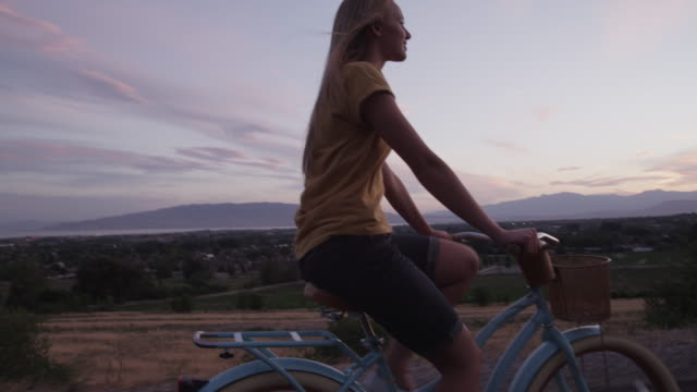 Tracking medium shot of young woman bike riding on road at sunset / Cedar Hills, Utah, United States