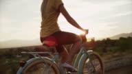 Tracking medium shot of young woman bike riding on road / Cedar Hills, Utah, United States