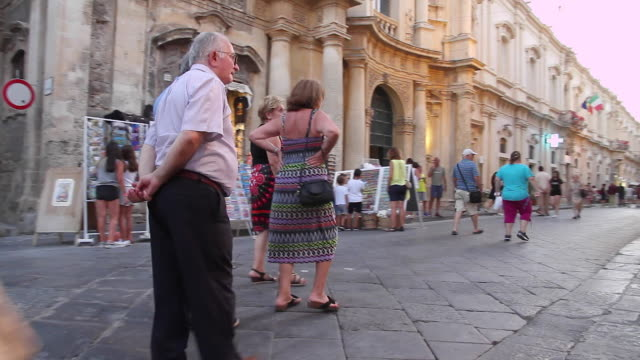 Tracking people and a woman walking a dog taking an early evening stroll along the beautiful streets of Noto, Sicily, Italy