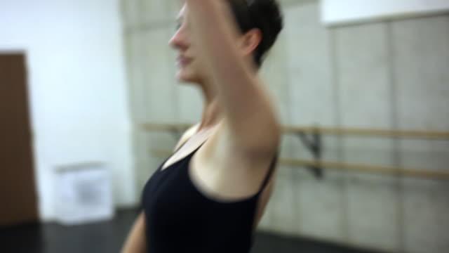 Tracking rack-focus shot of a female ballet dancer.