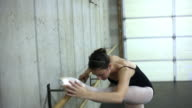 Tracking shof of a dancer exercising on a ballet barre.