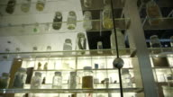 Tracking shot across small glass bottles filled with various materials on glass shelving, UK.