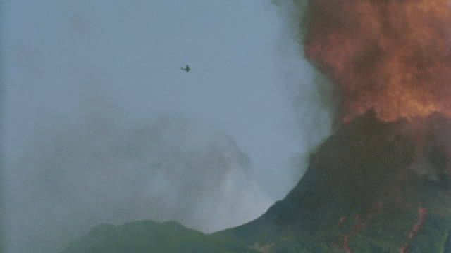 tracking shot airplane flying through flames of erupting volcano