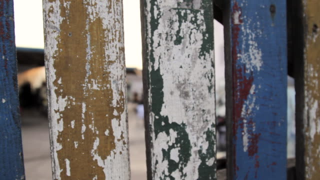 Tracking shot along a painted wooden fence.