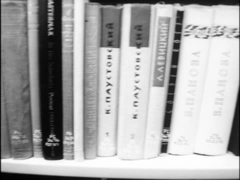 Tracking shot along a row of books in a library