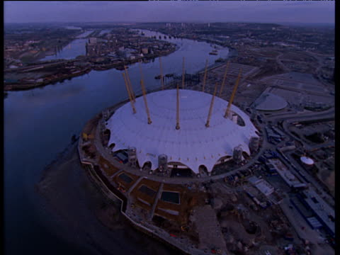 Tracking shot around the Millennium Dome construction site next to the River Thames, London; 1990's