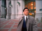 tracking shot Asian businessman in raincoat walking away from Municipal Building / NYC