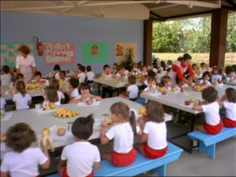 tracking shot children eating fruit in outdoor cafeteria at school / Brazil
