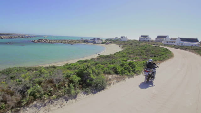 Tracking shot coastal town and biker on dirt road/ Western Cape/ South Africa