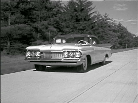 B/W 1959 tracking shot couple driving Oldsmobile on country highway