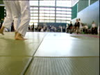 Tracking shot follows feet of Judo competitors as they fight London Towers England