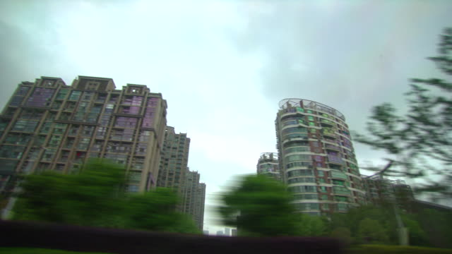 Tracking shot from a car as it travels past modern appartment buildings in the city of Nanjing.