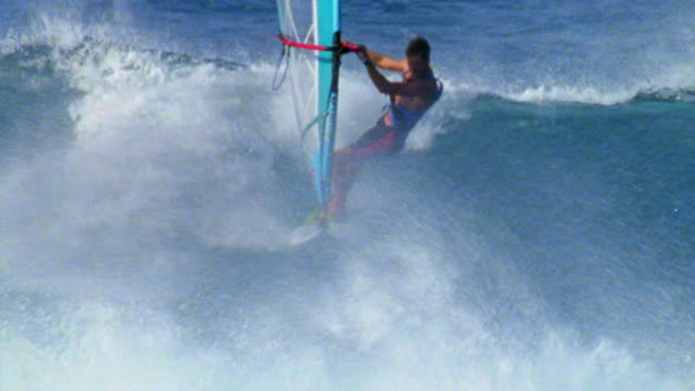 AERIAL tracking shot male windsurfer riding waves on ocean / Hawaii