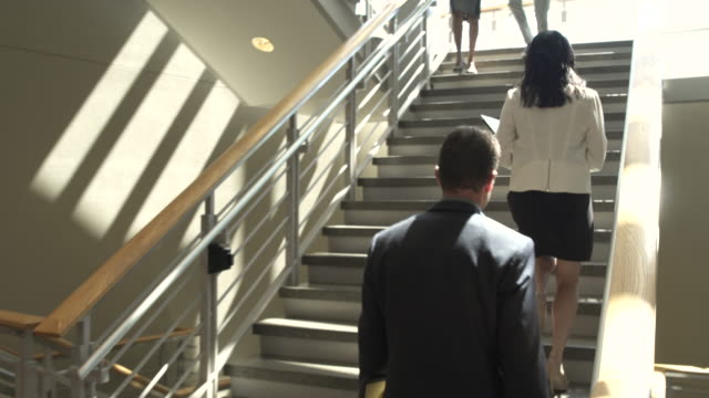 Tracking shot of a businessman walking up stairs