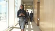 Tracking shot of a businesswoman walking down a corridor
